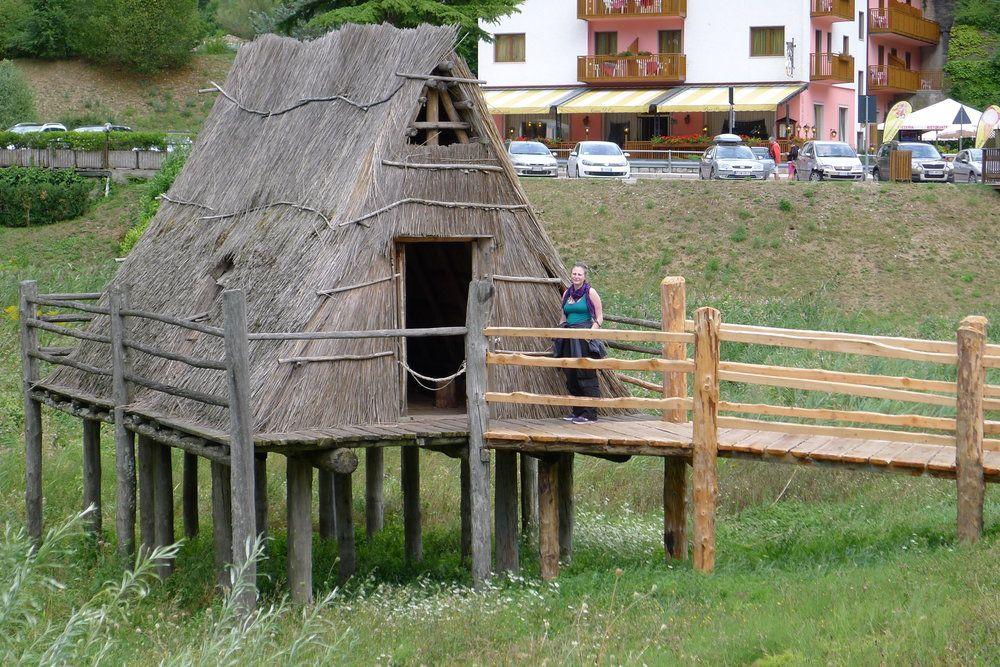 Eine Hütte auf einem Holzpodest. Die Hütte besteht aus nur einem Geschoss, das gleichzeit ein Dachgeschoss mit einem Giebel ist. Dieses Dach ist mit Stroh gedeckt. Die Tür befindet sich an der Giebelwand. alles besteht aus Holz. Eine Frau steht vor der Tür, so ist zu sehen wie klein diese Hütte ist.