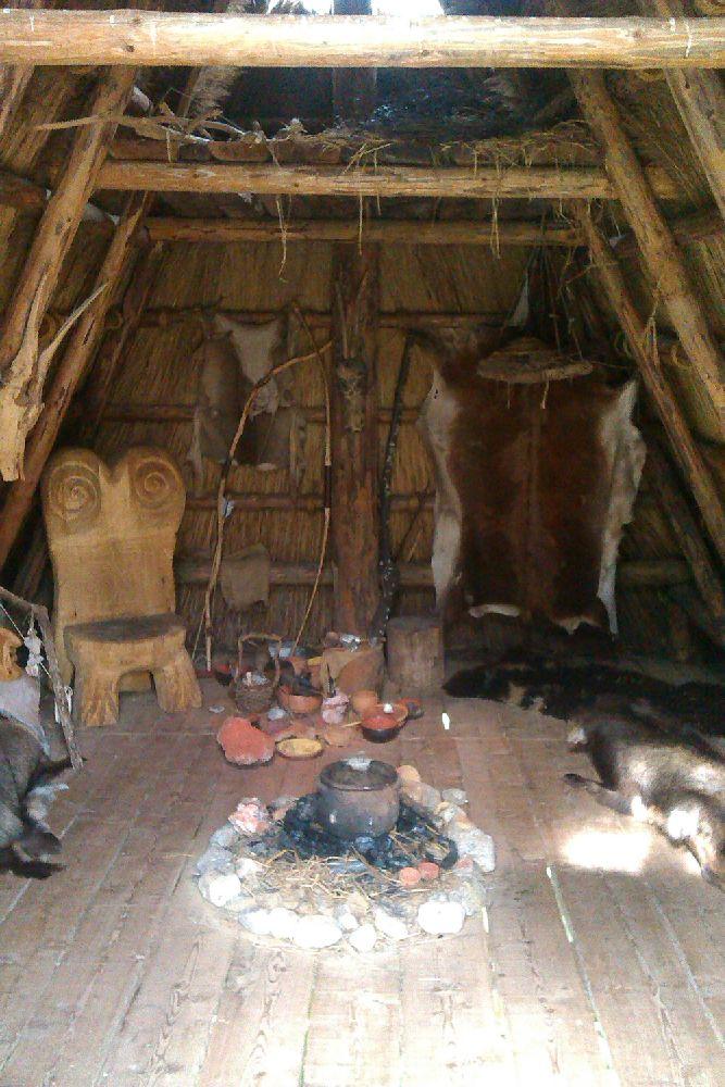 Eine Hütte des Pfahlbaumuseums am Ledrosee von innen. Die Hütte ist liebevoll ausgestattet mit Fellen, Schalen und Schüsseln und einem Prunkvollen Holzthron der mit geschnitzten Spiralen verziert ist. In der Mitte der Hütte befindet sich ein Feuer.