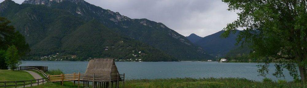 Im Hintergrund sind die Berge der Alpen zu sehen, zwischen ihnen liegt ein grünfarbener See, im Vordergrud steht eine hütte auf einer Plattform im see neben einer Uferwiese-