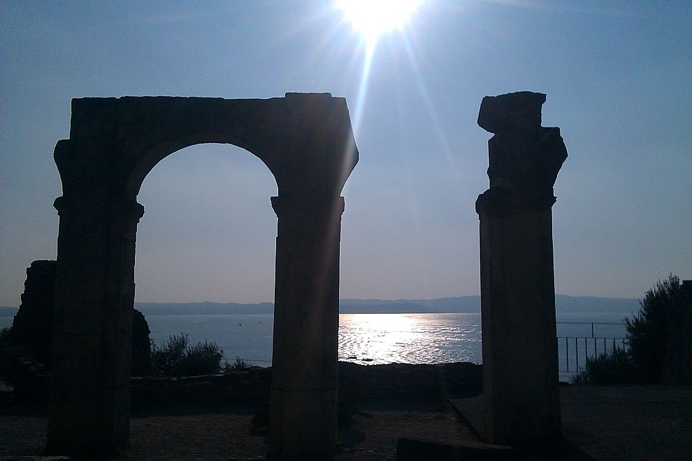Die Überreste der Ruinen an den Grotteen des Catull. Zu sehen ist ein Säulenbogen, und eine danebenstehende Beschädoegte Säule. Sie zeichenen sich als Schatten vor dem Wasser des Gardasees und einem blauen Himmel ab.