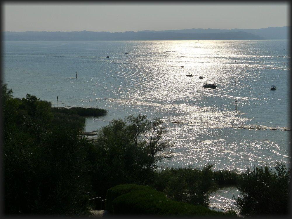Aussicht auf den Gardasee on den Grotten des Catull aus. einige sportboote sind auf dem Blauen wasser zu sehen. In ganz weiter Ferne liegen die Alpen.