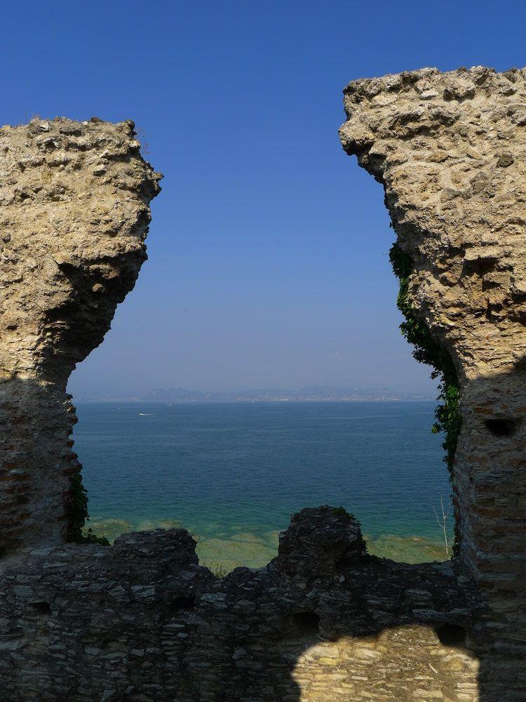 Blick durch die Ruinen der Grotten des Catull hindurch auf den Gardasee. Im Fordegrund sind links und rechts ziegelmauern, dahinter liegt Grünblaues Seewasser, und ein Blauer Horizont.