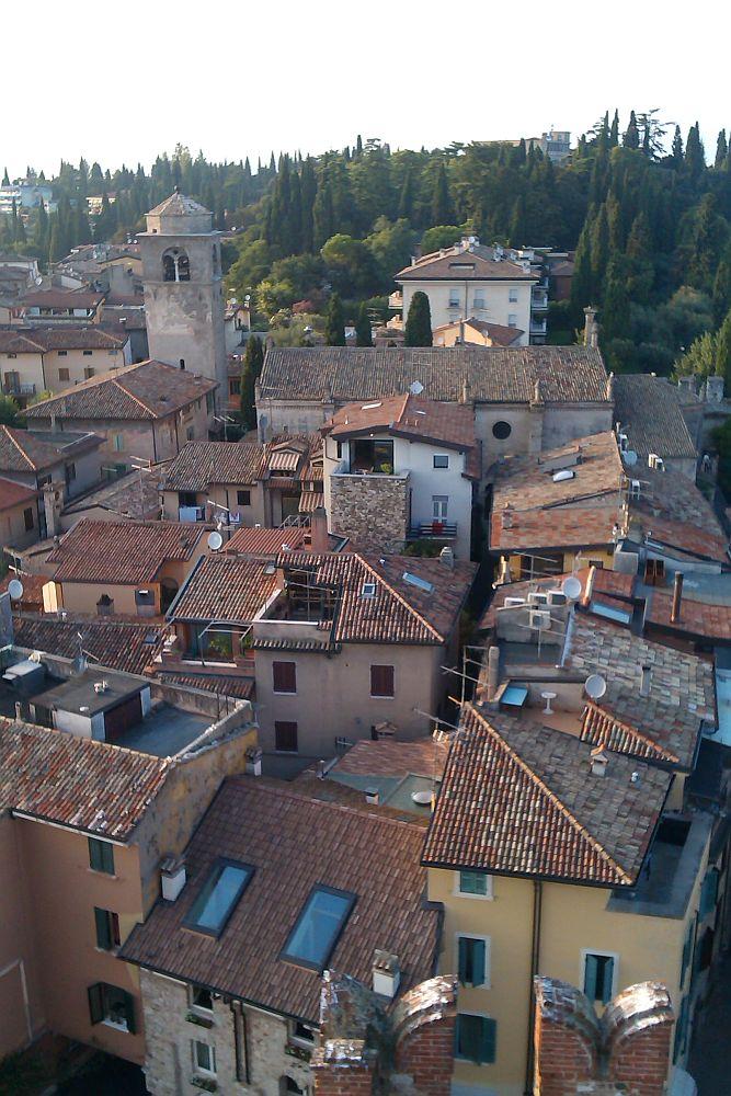 Mittelalterliches Dächermeer von Oben. Rotebraune Dachschindeln sind übrall auf den Dächrn des Ortes Sirmione und seiner Mittlalterlichen Mediteranen Siedlungslandschaft zu sehen. Eine Kirche mit einem Turm der ein halbrundes Dach hat ist zu sehenen, und viele enge Gassen. Am ende des Ortes beginte ein Wald aus Pinien.