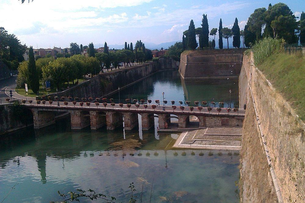 Im Vorderfrund bfindet sich die Mincinobrücke, im Hintergrund eine Bastion von dr aus diese Brücke übrblickt werden kann.