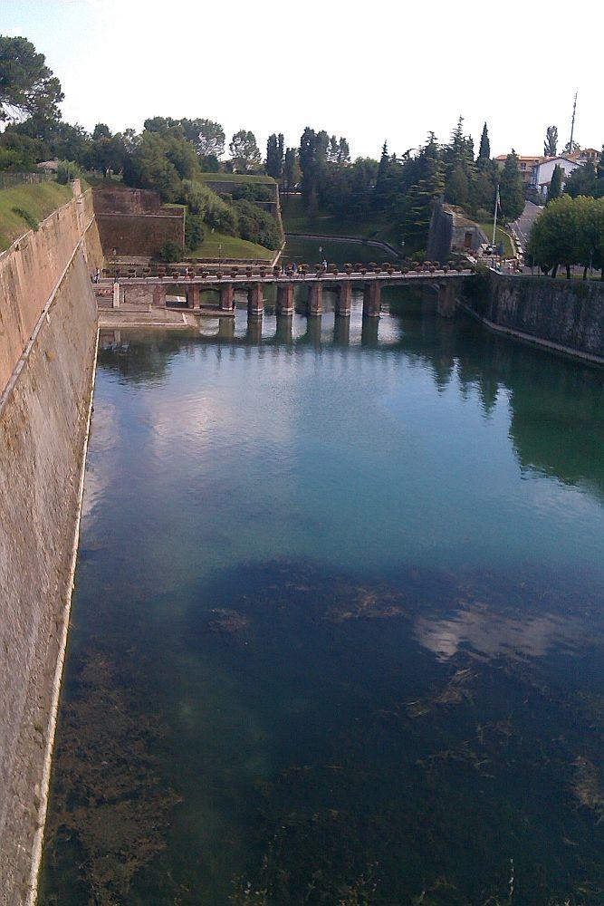 ine Brücke aus roten Zigeln verläuft übr den Blauen Mincino. Die Brücke ist mit roten Blumen Gschmückt. Deutlich zu sehen ist, das von zwi Bastionen einsehbar ist wer die Brücke überquert um zu der Festung zu gelangen.