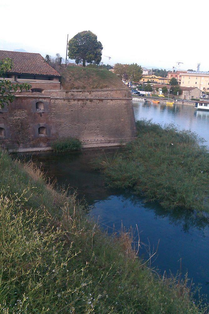 Eine aus roten Ziegeln gebaute Bastion, die in blaues Wasser hinein ragt. Die Bastion ist mit kleinen zugemauerten Bognfenstern ausgestattet, die in richtung des Wassers weisen.