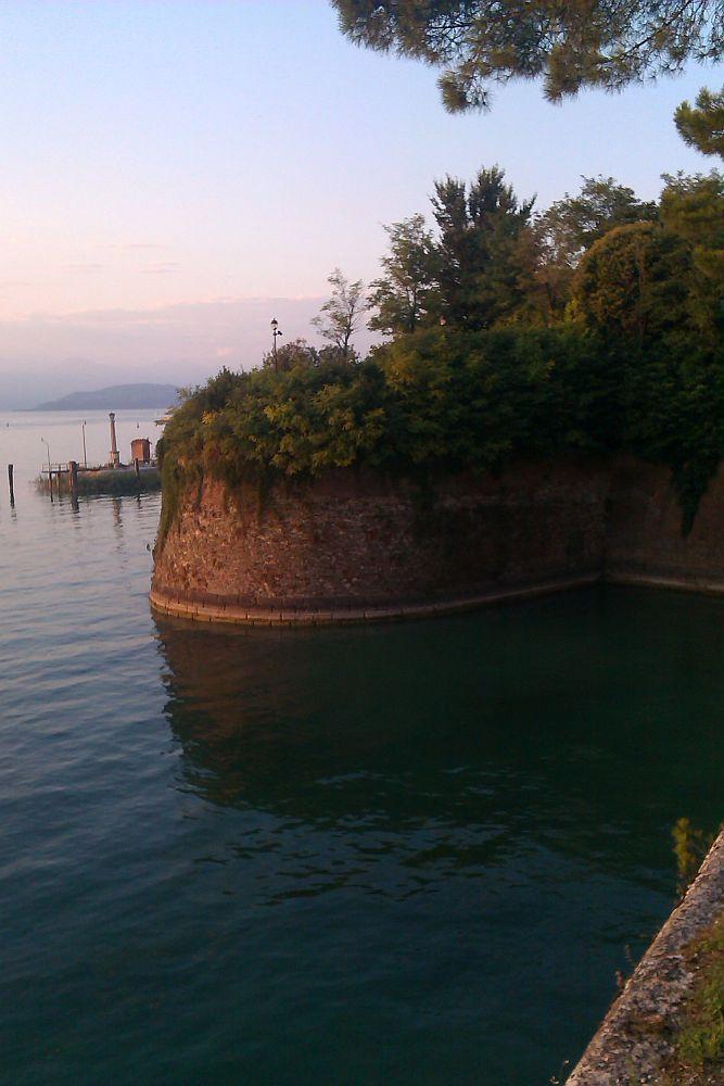 ine Bastion der Festung vo Pescira del Garda di in dn Gardasee hineinragt, der im Hintergrund zu shen ist. Die Rote Ziegelmauer wir von iner noch rotren Sonne angestrahlt. Der Bau ist grün überwuchert.