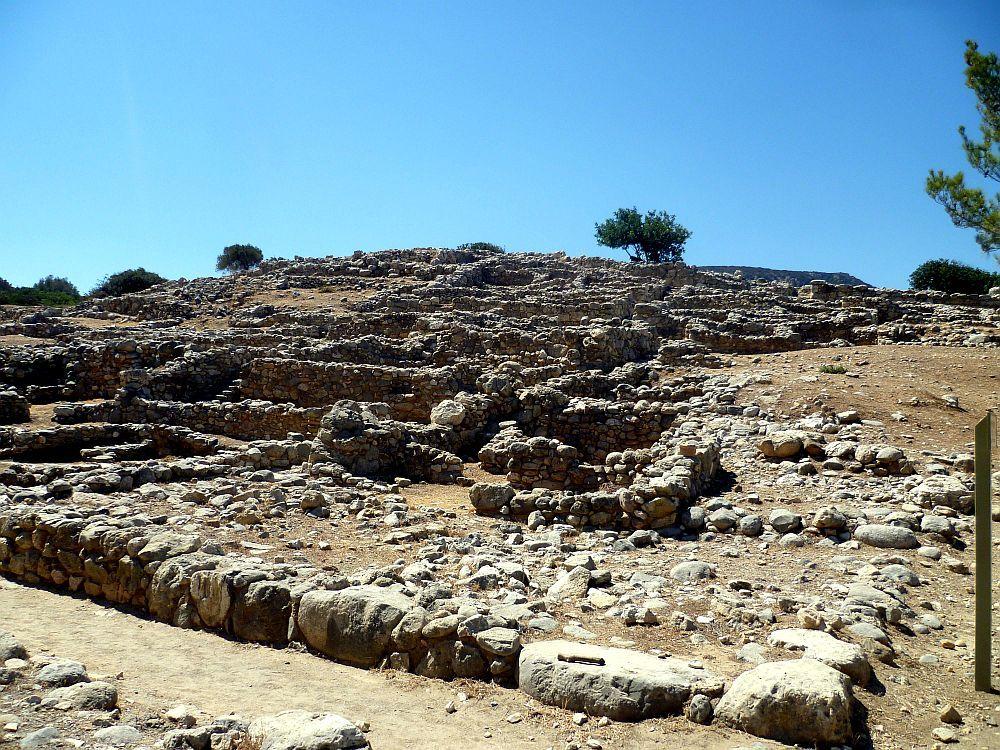 Die Ruienen von Gournia Türmen sich auf. Es handelt sich um etwa Kniehoh Hasuruienen die inn Berghang hoch klettr und so im Hintergrund immer höher liegen. Die Mauerreste bestehen aus Grauem Stein.