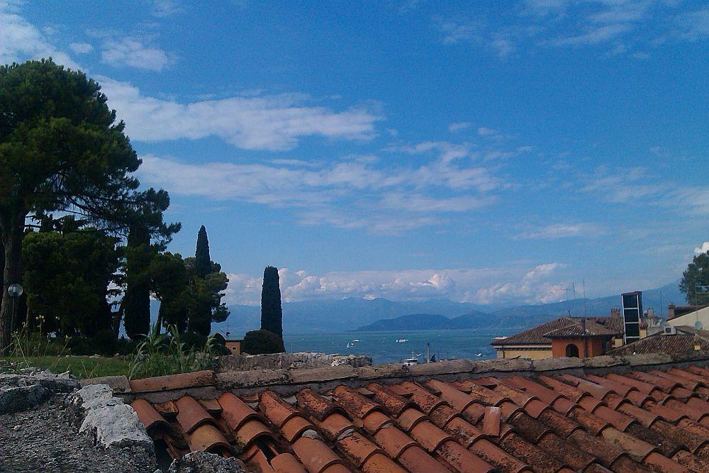 Der Blik über i rotes Dach dr alten Häusr von Psciera del Garda in richtung Alpen. Die Berg im Hintergrund und der Gardase im Vordergrund wirken wie in unendlicher blauer Horizont.