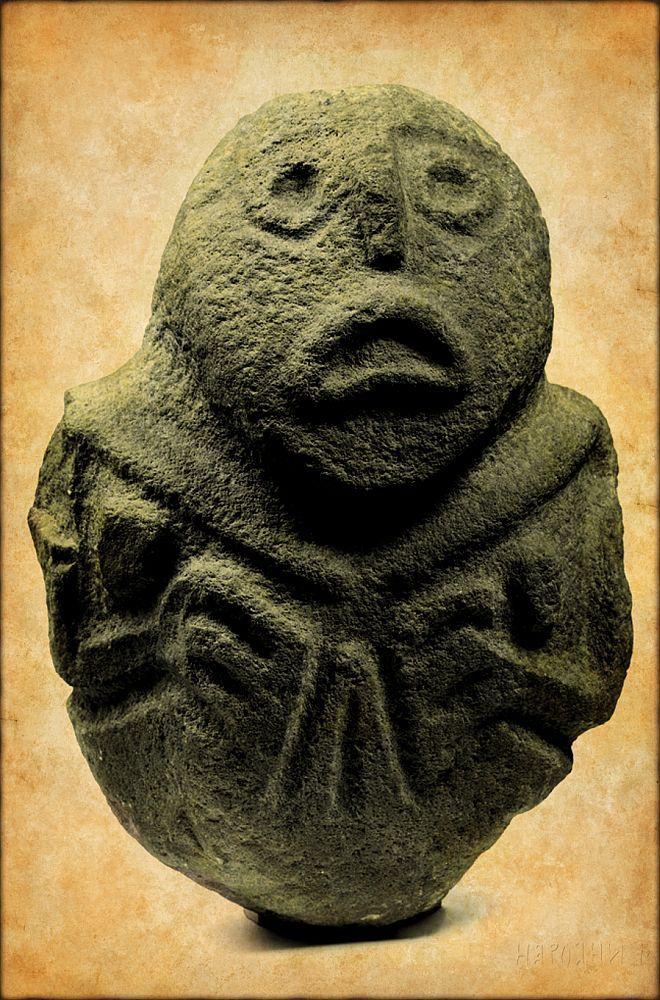 Eine Kopfskulptur mit hervorgearbeiteter Vulva. Die Dastellung des Gesichts erinnert an einen Karpfen.