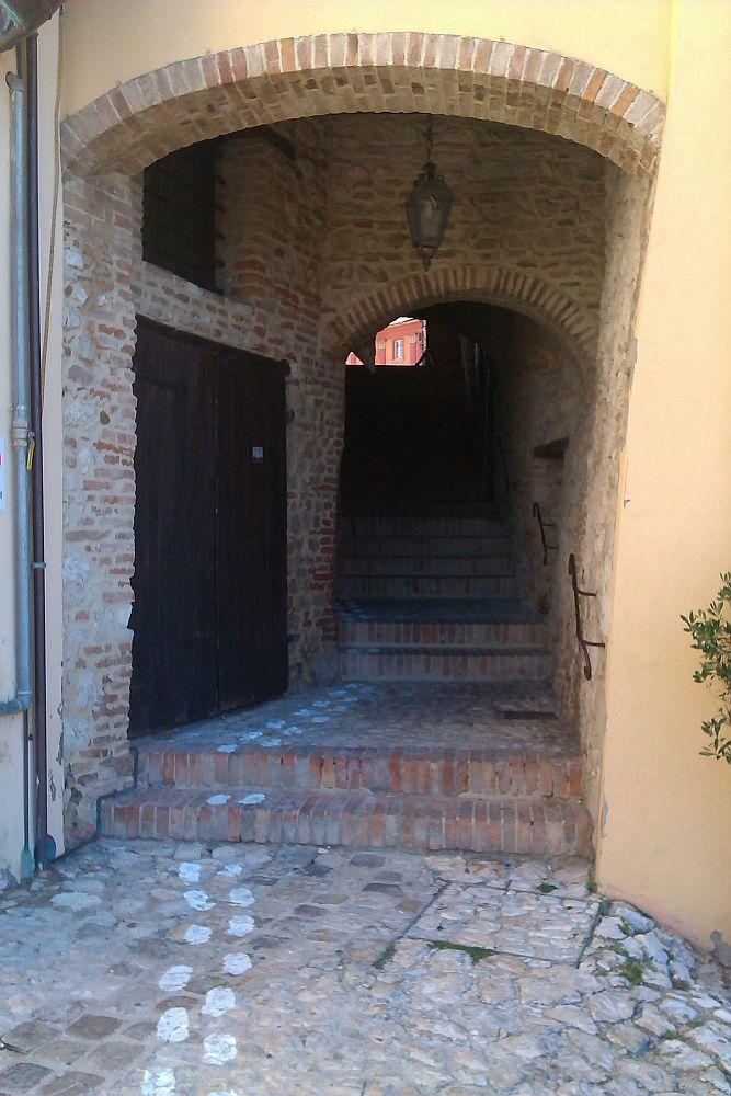 Ein Mittelalterlicher Durchgang der Zwischen Häusern druch führt. Er ist durch eine Treppe begehbar. Mit weiser Frabe sind Fussuren auf den Boden gemalt die anzeigen,d as man dort hindurchgegehn darf.