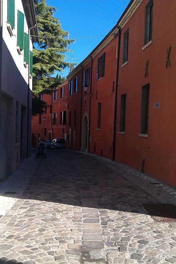 Eine Gasse, die sich in einem Bogen erstreckt. Die Gasse ist sehr schmal und mittelalterlich gepflastert, auf einer Seite sind alle Häuser Rot angemalt.