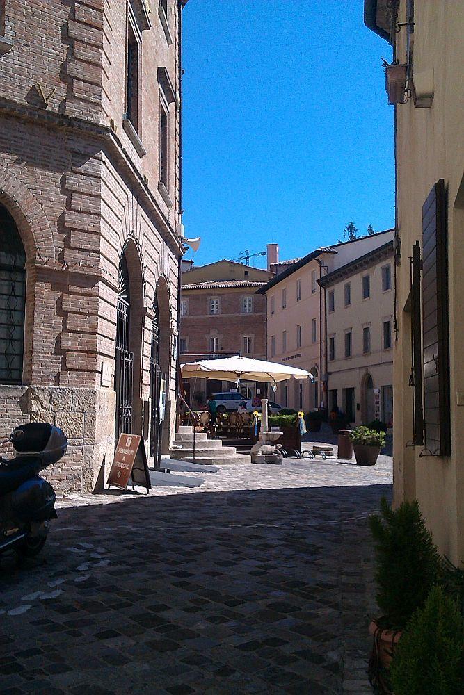 Links und rechts sind Häuser eine schattigen Gasse. Geradeaus erstreckt sich ein luftiger kleiner Platz auf den die Sonne scheint. Dort ist der Sonnenschirm von einem Café zu sehen.