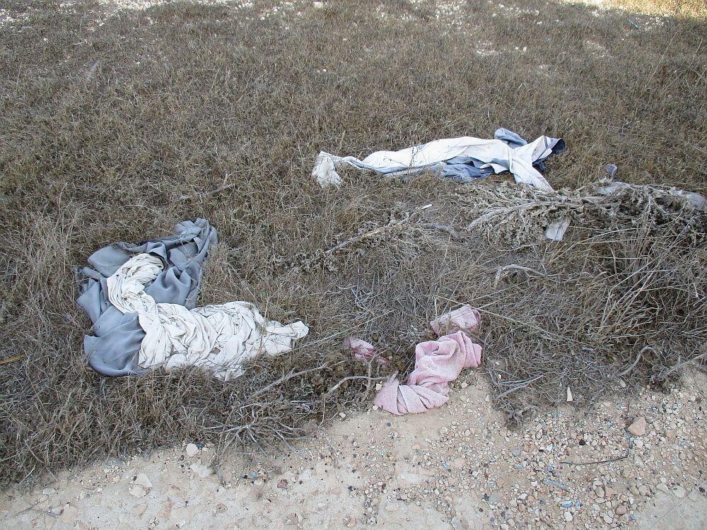 Kleidungsstücke liegen unter einer ausgetrockneten Wiese zum Teil im Sand verschüttet.