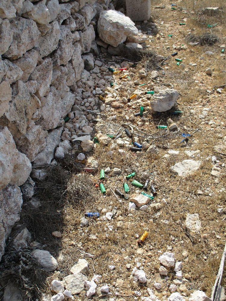 Neben einer Mauer liegen im Sand in einer verdörrten wiese vile verschidenfarbiege Munitionshülsen herum.