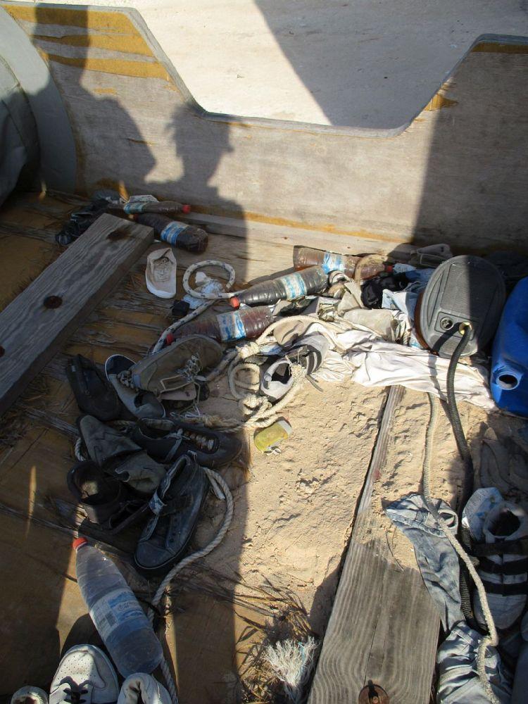 Ein Schlauchoot von innen Es ist mit Sand überschüttet, überall liegen Schuhe herum, und Plastikflaschen.