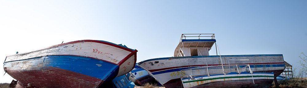 Bppte liegen im Wüstensand. Im Vordergrund sind zwei Holzbppte zu sehen die mit dem Bug zueinander liegen, und dahinterliegende weitere Boote verdecken. Das rechts bot ist weis blsu rot gestrichen das linke in weis und blau.