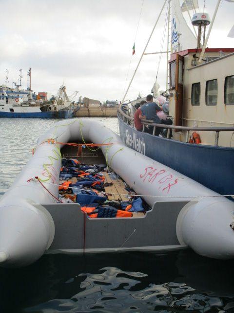 Ein Schlauchboot in grau in dem ganz viele Schwimmwesten liegen die Orange leuchten.