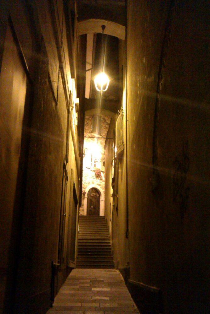 Eine Sehr Enge Gasse bei nacht. Die Häuser links und rechts sind dunkel, am Boden ist pflasterstein und eine Treppe zieht sich zwischen den häusern durch, die so dich beeinander stehen, das gerde eine Persohn hindurch laufen kann. Die Ganze Szenerie wird von einer einzigen Strassenlaterne beleuchtet.