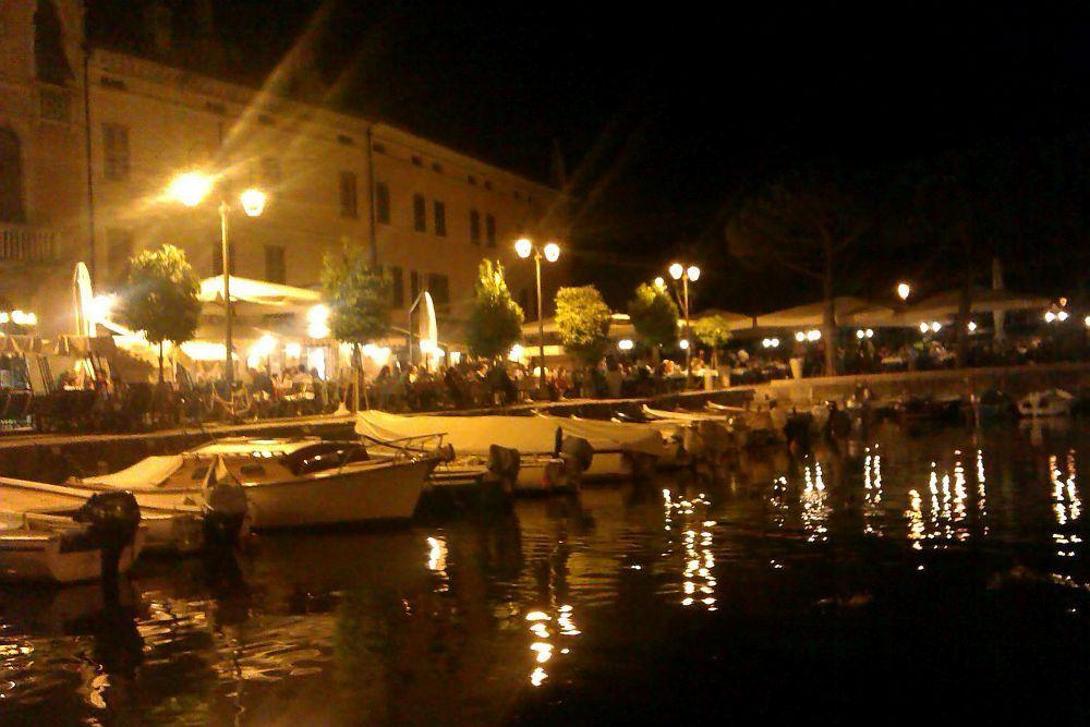 Das Hafenbecken im Dunkeln. Alles ist hell gelb-orange erleuchtet. am hefanbecken ist eine riesen Feier.