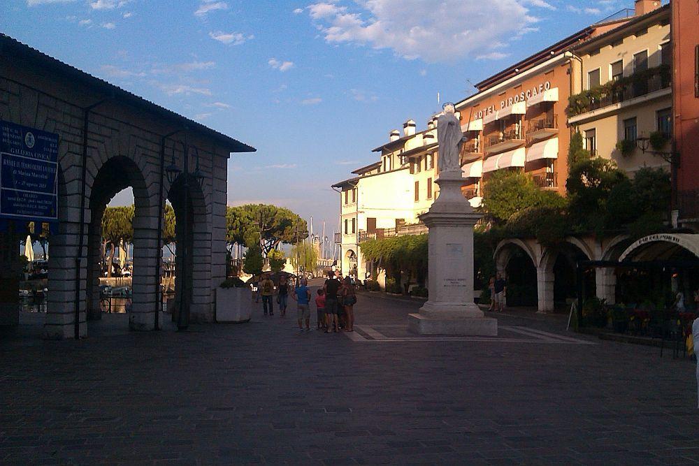 Ein platz auf dem rechts ein Gebäude das nur aus bögen besteht zu sehen ist, links befinden sich Wohnhäuser. in der mitte eine Heiligenstatue und im Hintergrund ein Hafenbecken.