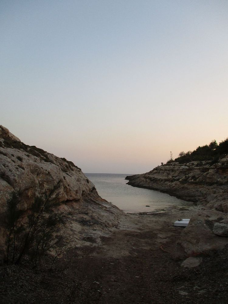 Eine Bucht an einer Steilküste. Es gabt zwischen den klippen einen kleinen Strand. Am Horizont sind letzte Sonnenstraheln zu sehen.