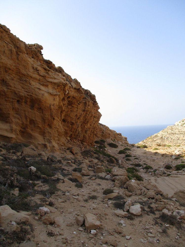 Ein Canyon aus rotem Stein. Im Hintergrund das Meer