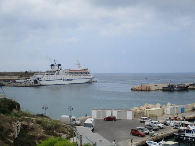Ein hafen der links und rechts durch Molen Eingegränzt ist. Am linken Kai ist ein großes Schiff zu sehen.