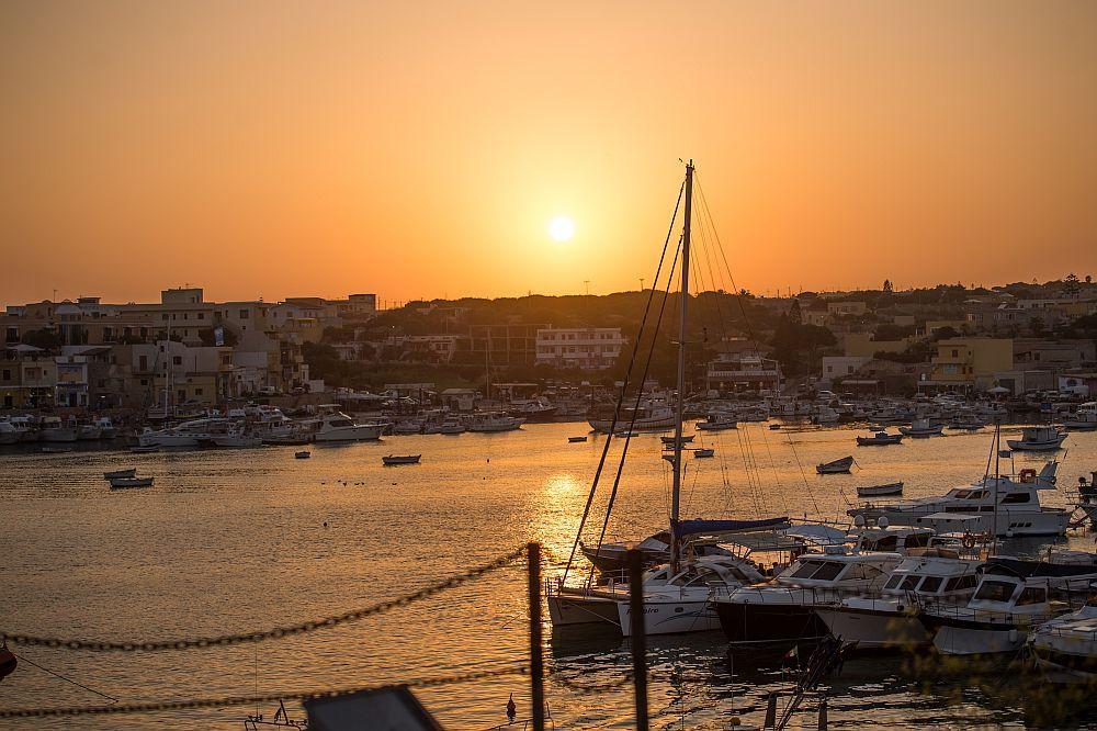 Der Himmel ist durch die Sonne in ein starkes Orange getaucht. Darunter liegt ein Hafenbecken das ebenso Orange leuchtet.