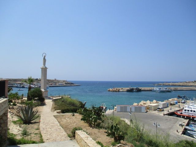 Der Ausblick auf ein Hafenbecken das durch zwei aufeinander ausgerichtete Molen eingegrenz und vom Meer abgetrennt wird. Am Hafen steht eine Skulptur auf einer Säule.
