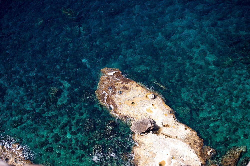 Eine Landzunge zieht sich in durchsichtieges Türkiesblaues Meerwasser durch das man bis zum Bpden blicken kann.