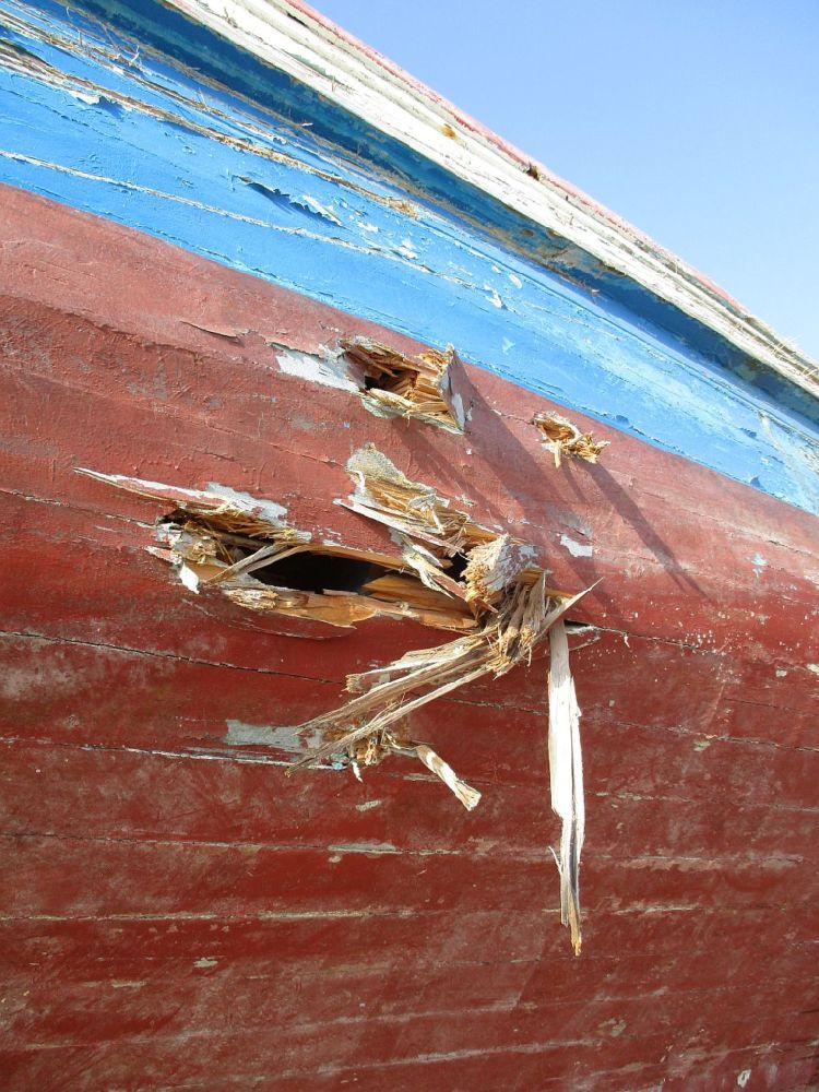 Ein Bug eines Holzbootes. Grosse Löcher sind in den Bug gerissen.