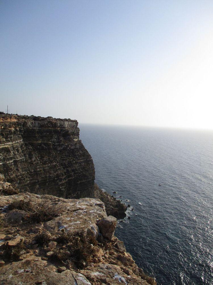Die Steile Küste von Lampedusa. Eine Steilklippe Ragt ins Meer, sie ist mindesten 80 Meter Hoch. Die Stratigrafie des Gesteins lässt sich gut erkennen.