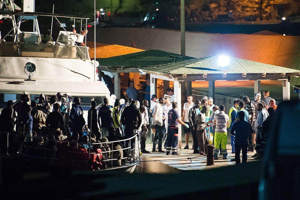Ein Schiff ist in der Nacht an Beleuchteten Kai, Menschen Warten das sie Aussteigen können. Am Kai stehen ganz viele Sanitäter.