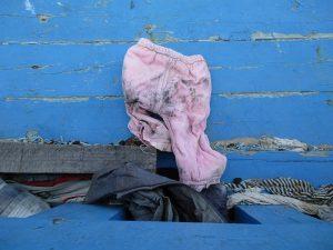 Eine Babyhose in rosa liegt auf den Planken eines Blau gestrichenen Holzbootes. Es ist sehr dreckieg.