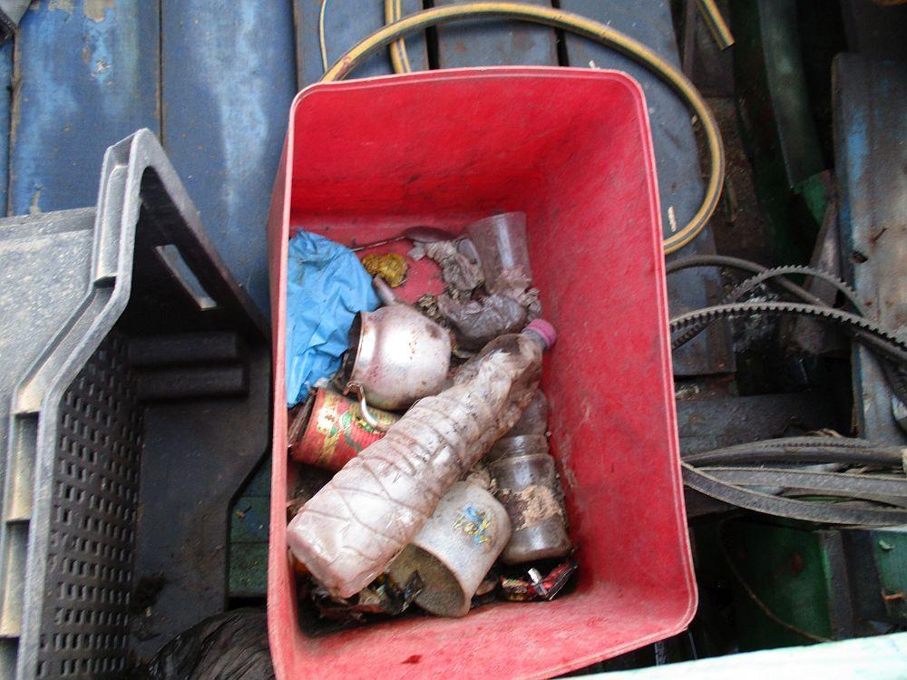 Eine Rote Plastikkiste Auf einem Schiff. Der Inhalt ist zu sehen: Eine versandete Wasserflasche eine Teekanne eine Tomatenmardose und ein paar Teebecher.