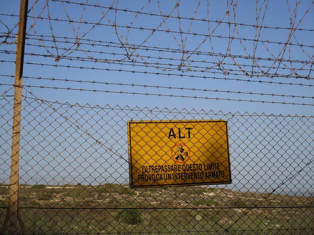 Ein Gelbes Warnschild mit itelienischer Aufschrift, das vor einem Scheißbefehl warnt. Ein Piktogramm in der Mitte zeigt einen Soldaten der eine Waffe auf die betrachter des Schildes richtet.