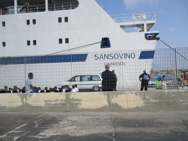Die köpfe vieler dunkelhäutieger Menschen die hinter iner niedriegen Betonwand auf dem boden sotzen sind zu sehen. Sie sind umringt von einigen wenigern italienischen Polizisten. Hinter ihnen steht die Hafenfähre von Lampedusa zum Festland.