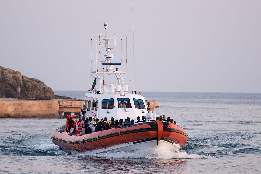 Ein Rettungsboot kommt herbeigefahren. Auf dem Boot sitzen unzählig vieledDunkelhäutiege Menschen-