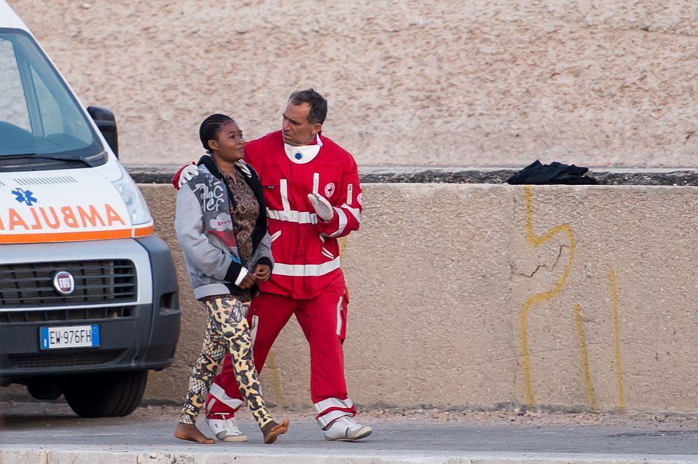 Eine schwarze Frau läuft Barfus an einem Rettungwagen Vorbei. Ein Sanitäter legt einen Arm um sieh und macht mit der anderen Hand eine beruhigende Handgeste. Die Frau hat einen Gesichtsausdruck, zwischen glück, trauer, angst, befreiung. Man kann sehen, das sie nicht glauben kann, das sie noch Lebt.