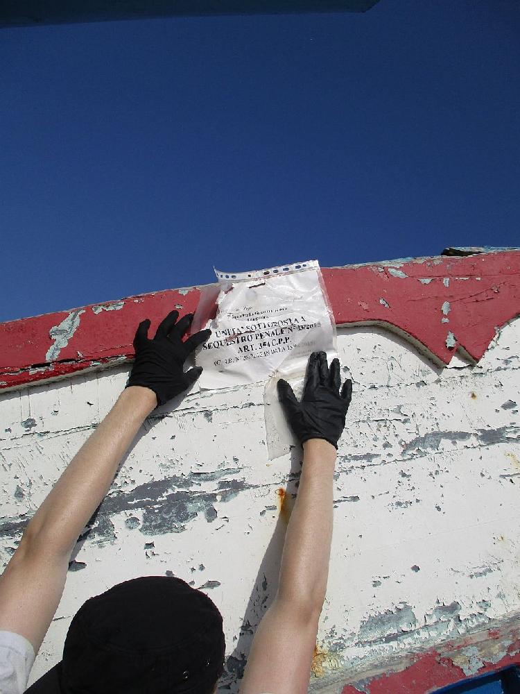 Zwei häne halten ein schild aufgeklappt das an einem Schiff mit einer reiszwecke befestiegt wurde. Es handelt sichum einen Zettel in einer Klarsischtfolie. Auf dem Schild steht auf italiensch, die Aservatennummer und das Datum an dem das schiff gekentert ist.