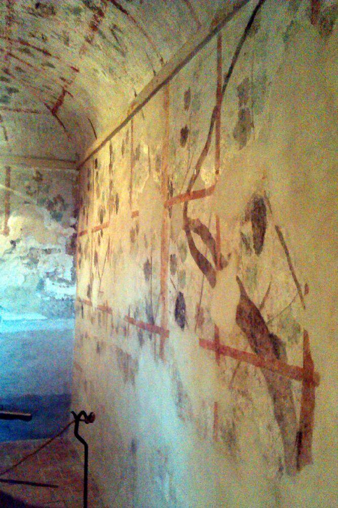 Eine Kellerwand aus verkalten Bchgeförmigen Katakoben ist mit Roten linien kariert bemalt.