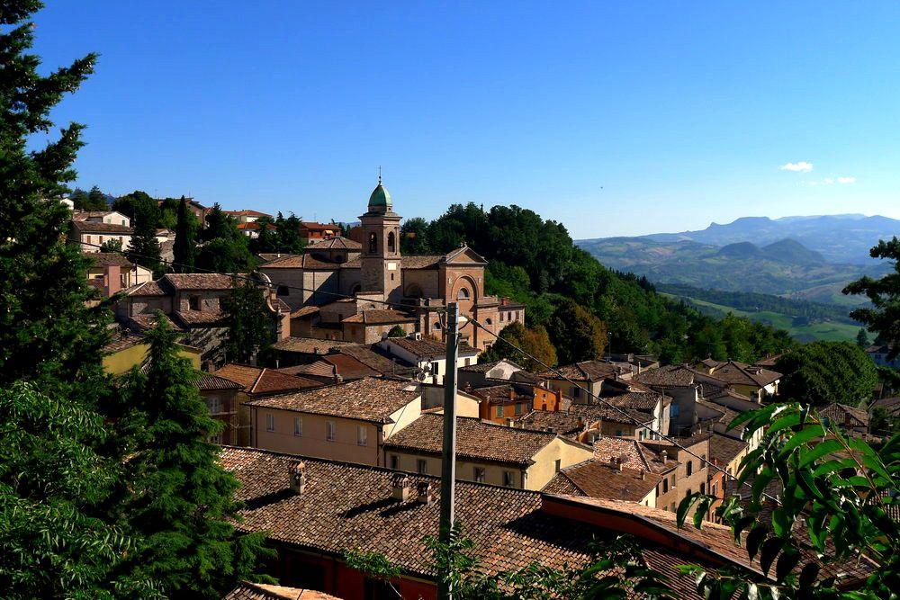 Der Himmel ist strahlend Blau über der mittelalterlichen Siedlung, sie kuschelt sich an einen grünen Hügel.