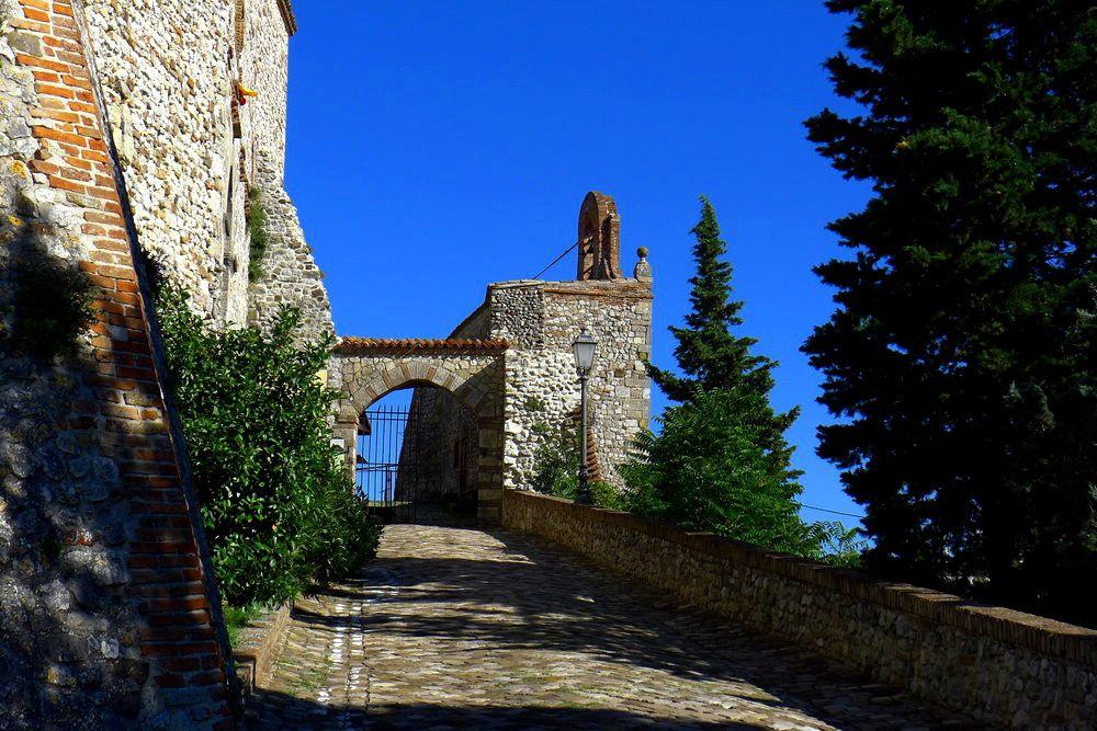 Ein grob gepflasterer Weg geht steil einen Berg hoch. Am ende des Weges ist ein Tor aus Stein mit einem geöffneten Gitter.