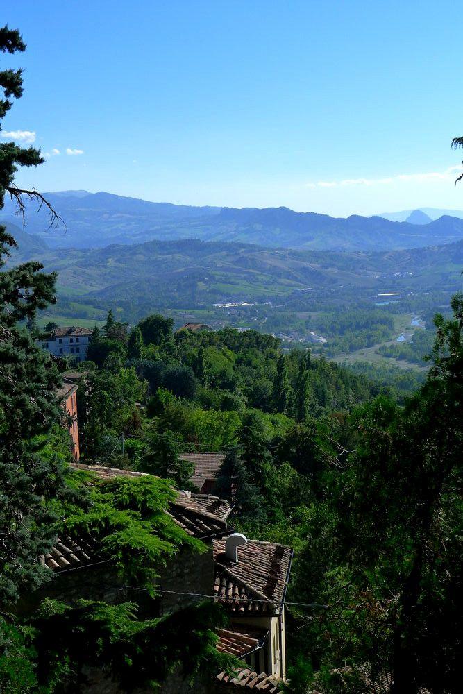 Der Blick von einem Grünen Berg aus in ein Grünes Bergieges Hinterland mit Zypressenwäldern.