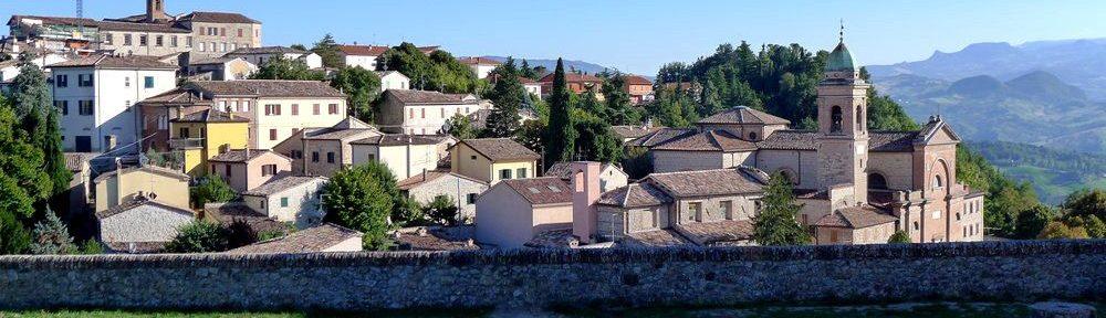 Panoramaaufnahme vom Ort Verruchio vom oben aus gesehen. Der Ort klettert einen grünen Hügl hoch. Viele Mittelalterliche Häuser kuscheln sich auseinander.