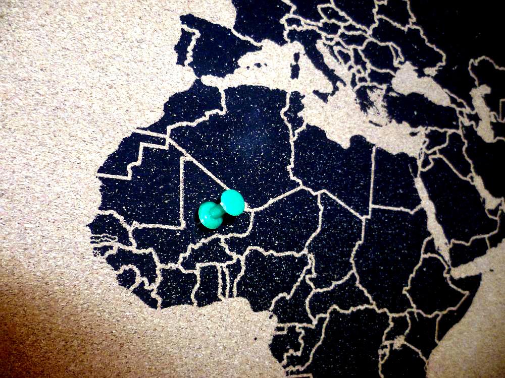 Ausschnitt aus einer Karte, Westafrika und teile Europas sind zu sehen. Die einzelnen Länder sind schwarz dargestellt. In dem Land Mali steckt eine grüne Reißzwecke