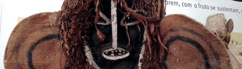 Eine Tikunamaske mit einen ovalen Gesicht. Sie besteht aus schwarzen Holz, das mit weisr Farb nachgezeichnet ist. Ohren Haare und ein Bart sind aus braune, Leinensoff gefertiegt. Die Wangen der Maske sind Rot angemalt.