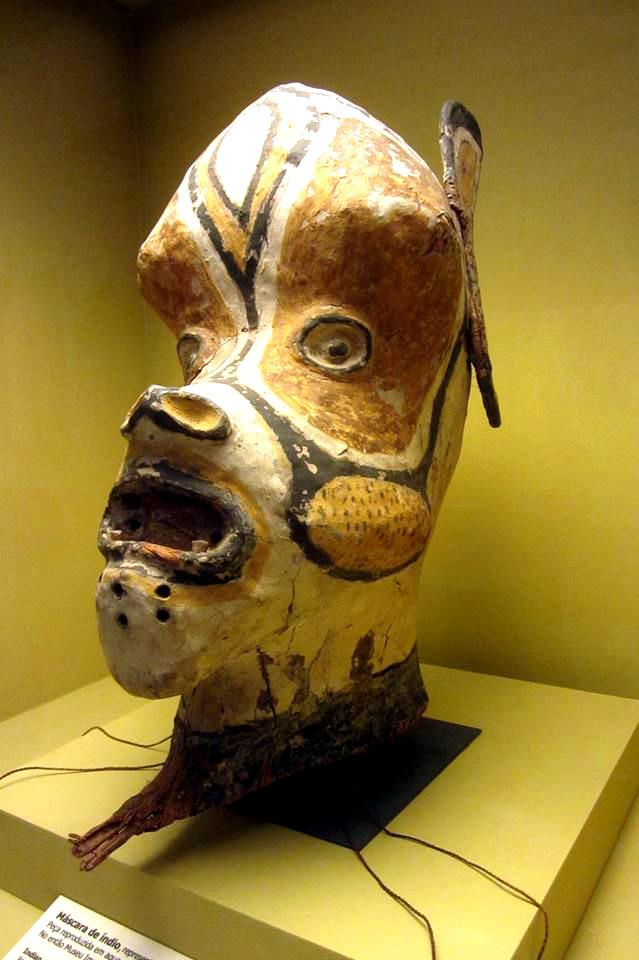 Eine Maske mit affenförmigen Gesicht. und großen Ohren. Sie ist rot-gelb-schwarz-weiß bemalt. Die Kopfform ist skuril überzogen.