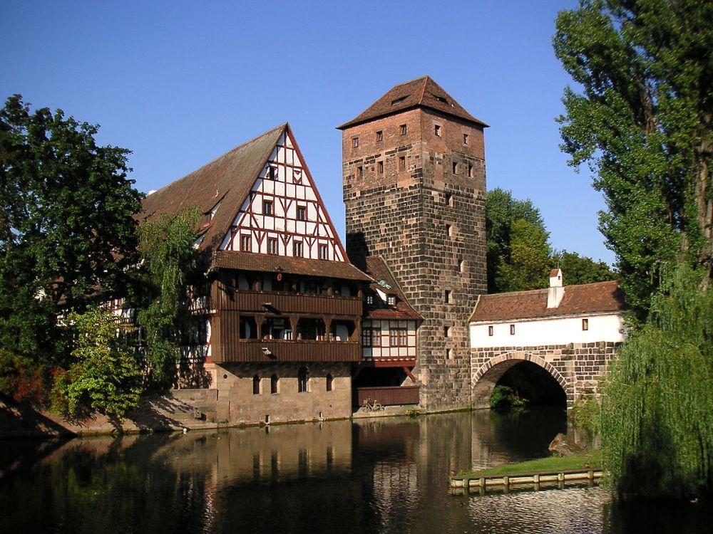 Ein Fachwerkhaus mit einem Steinturm in Nürnberg. Die Gebäude sich dierekt am Fluss gelegen